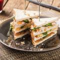 Club sandwich met gerookte kip, oude kaas, bacon en Hero Abrikozen Jam
